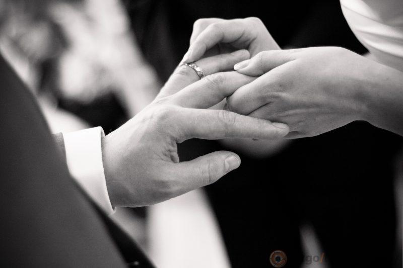 Bride putting ring on groom finger