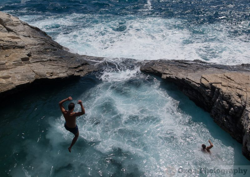 man jumping from the cliff into Giola, Thassos, Greece
