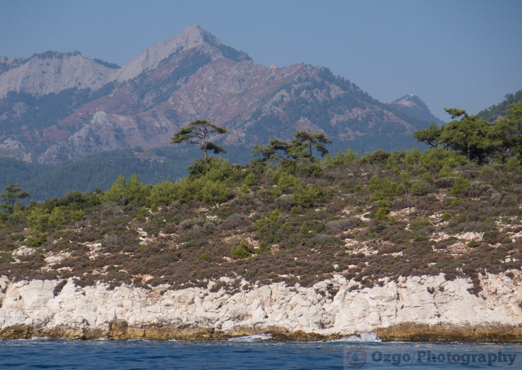 Rocky shore and mountains in the background in Thassos, Greece